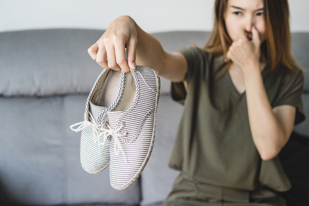 Foto de Young asian woman holding a pair of smelly and stinky shoes at home - Imagen libre de derechos