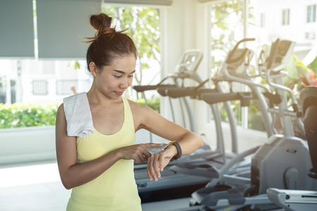 Foto per Young asian woman using smart watch in gym, Fitness, training lifestyle concept - Immagine Royalty Free