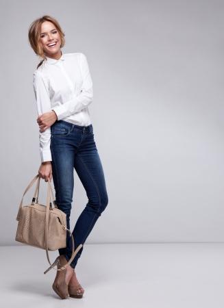 Photo for Beautiful woman holding a handbag - Royalty Free Image