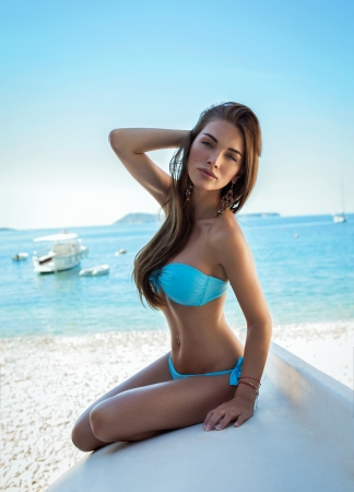 Foto de Sexy woman wearing blue swimwear on the beach - Imagen libre de derechos