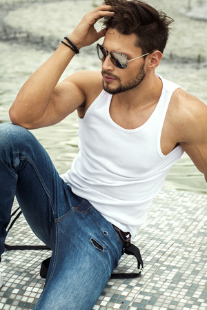 Foto per Sexy man in aviator sunglasses touching his hair - Immagine Royalty Free