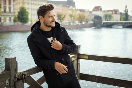 Photo for Photo of handsome smiling man in black coat in autumn scenery - Royalty Free Image