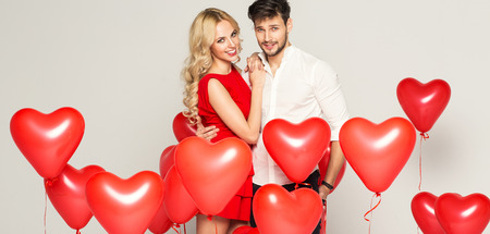 Photo for Fashionable couple with ballons heart hugging at each other - Royalty Free Image