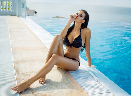 Photo for Beautiful woman wearing black bikini by the pool in summer scenery - Royalty Free Image
