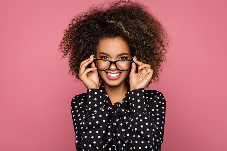 Photo pour Beauty portrait of a young black healthy woman holding glasses and looking at camera  - image libre de droit