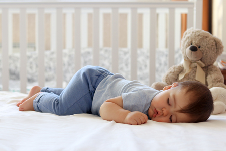 Foto de Funny baby sleeping on his stomach on bed at home. Child daytime bottom up sleeping position - Imagen libre de derechos