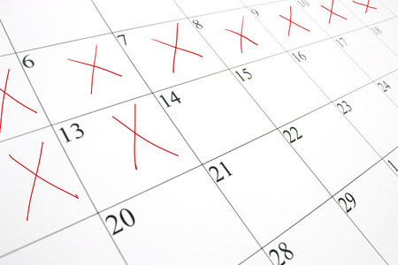 Photo for close up of a white calendar page with some of the days crossed off with a red X - Royalty Free Image