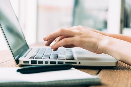 Foto de Woman working with laptop placed on the wooden desk - Imagen libre de derechos