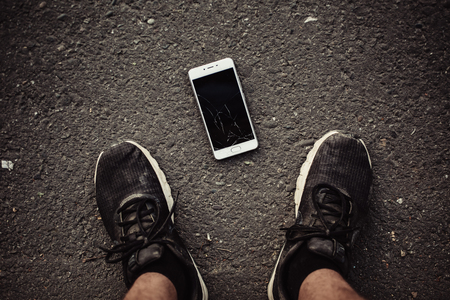 Foto de Legs and a smartphone with a broken screen on a dark background. The view from the top. - Imagen libre de derechos