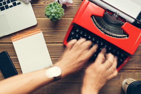 Photo pour Top view close up of mans hands using vintage red typewriter placed on wooden desk - image libre de droit