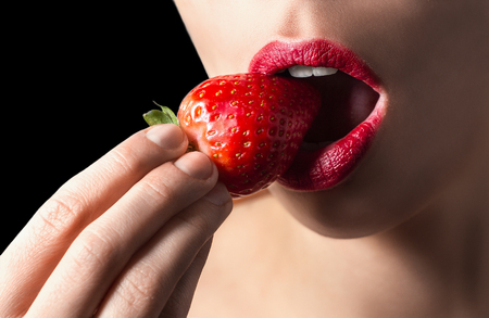 Foto de Sexy lips eating strawberry. Passion and desire. Strawberry and lips are red. Sexy and nude on black background. Sexy lips, white teeth, delicious strawberry. - Imagen libre de derechos