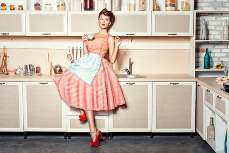 Photo pour Woman in an apron in the kitchen drinking from a cup and waving. - image libre de droit