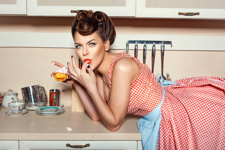 Photo pour Girl eating cake and licking her fingers, she was lying on the table. - image libre de droit