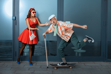 Foto de Funny old man riding a skateboard, standing next to in surprise woman. - Imagen libre de derechos