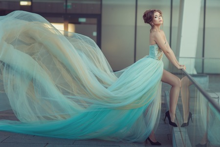 Photo for Young girl's dress gently blue color, it flying in the wind. - Royalty Free Image