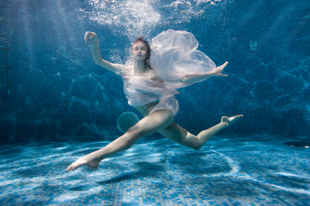 Photo for Woman dances underwater sports dance, her dress fluttering under the water. - Royalty Free Image