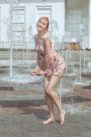 Photo for Wet woman dries her dress, she plays in a fountain and gets wet. - Royalty Free Image