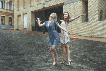 Photo for Women are happy with the rain, they are happy and dancing in the rain. - Royalty Free Image