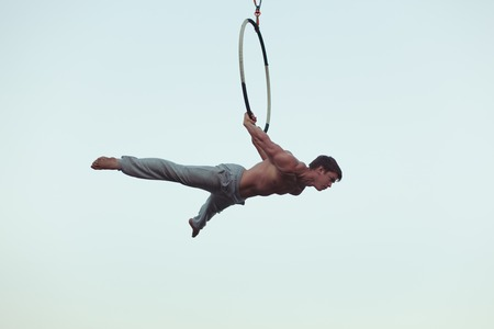 Photo for Man is an acrobat high in the sky, he shows the performance on the ring. - Royalty Free Image