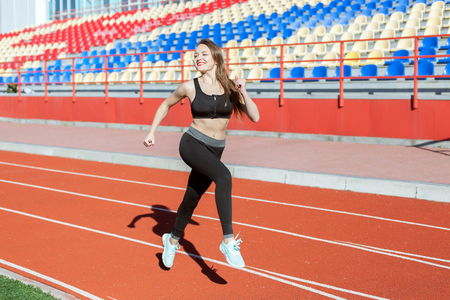 Photo for Young beautiful woman is engaged in the stadium. She is running. - Royalty Free Image