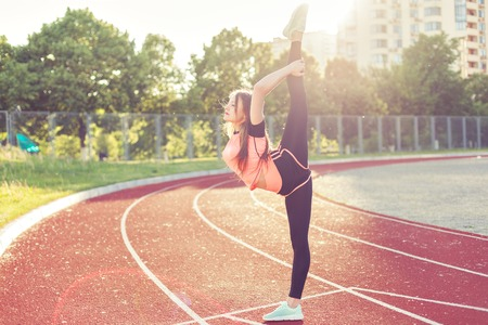 Photo pour Young woman doing stretching. Sports training at the stadium. - image libre de droit