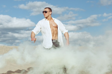 Photo for Young man in a white shirt stands among the smoke in the desert. Hi holds cigar. - Royalty Free Image