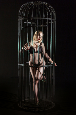 Photo for A young woman inside the cage, wearing erotic lingerie mesh. Sex games of humiliation and submission. - Royalty Free Image