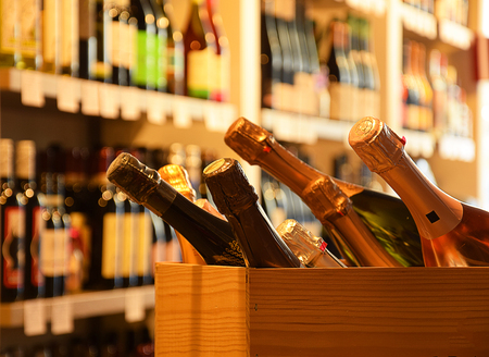 Foto de Wine bottles on wooden shelf in wine store - Imagen libre de derechos