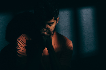 Photo for Prisoner man in dark cell depressed or praying - Royalty Free Image