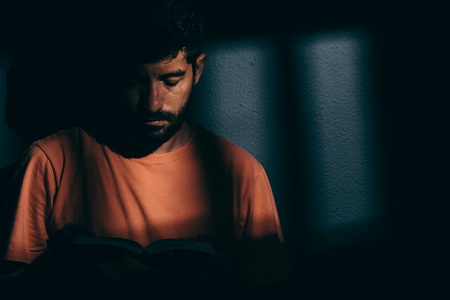 Photo for Prisoner man in dark cell reading a book or bible - Royalty Free Image