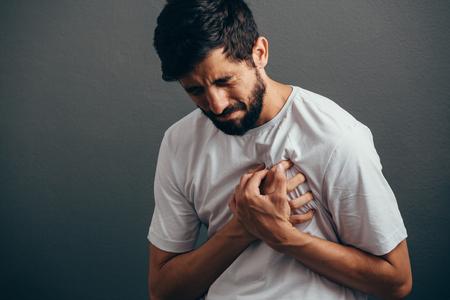 Foto de People, healthcare and problem concept - close up of man suffering from heart ache over gray background - Imagen libre de derechos