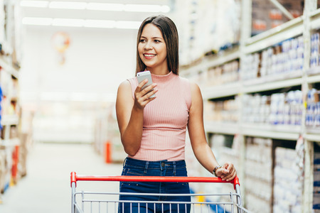 Photo pour Woman using mobile phone while shopping in supermarket - image libre de droit