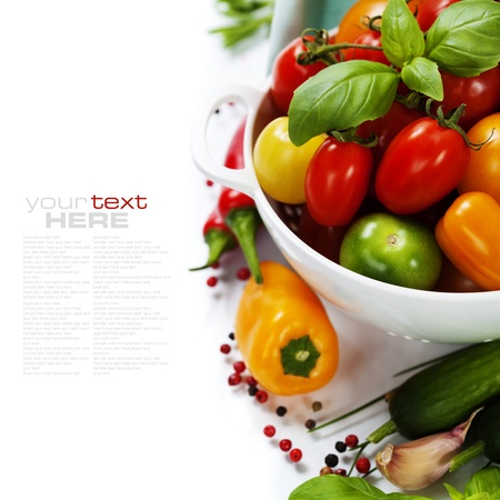 Photo pour Assorted colorful tomatoes and vegetables in colander on white background - healthy eating concept (with easy removable sample text) - image libre de droit