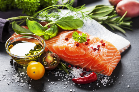 Foto de Delicious  portion of fresh salmon fillet  with aromatic herbs, spices and vegetables - healthy food, diet or cooking concept - Imagen libre de derechos