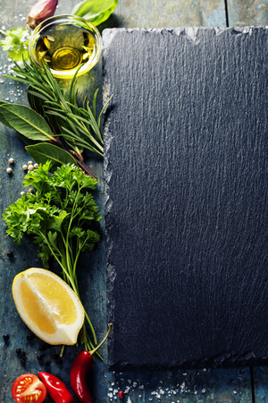 Photo for Food background, with herbs, spices, olive oil, salt, lemons and vegetables. Slate and wood background.  - Royalty Free Image