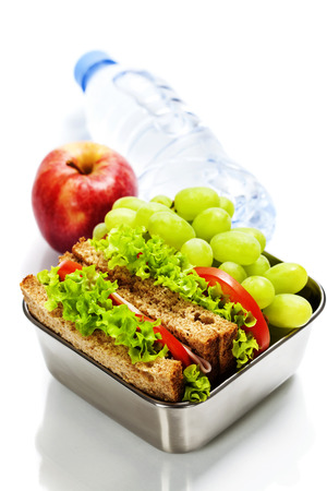 Photo for Lunch box with sandwiches, fruits  and water on white background - Royalty Free Image