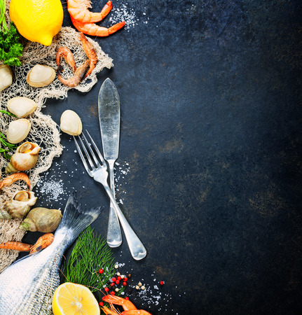 Delicious fresh fish and seafood on dark vintage background.
