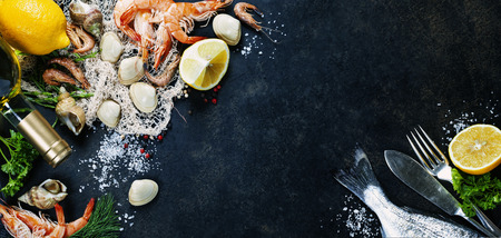 Foto de Delicious fresh fish and seafood on dark vintage background.  - Imagen libre de derechos