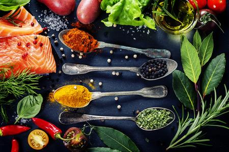 Foto de Delicious  portion of fresh salmon fillet  with aromatic herbs, spices and vegetables - healthy food, diet or cooking concept - Imagen libre de derechos