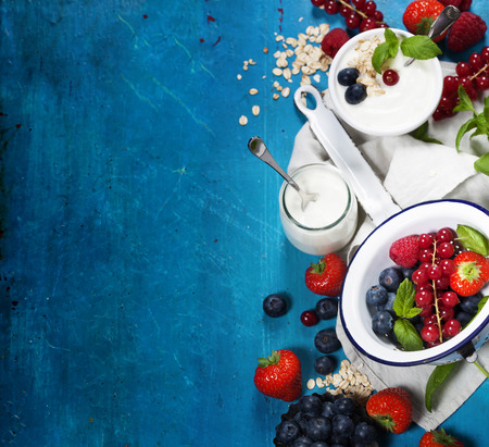 Foto de Healthy breakfast - yogurt with muesli and berries - health and diet concept - Imagen libre de derechos