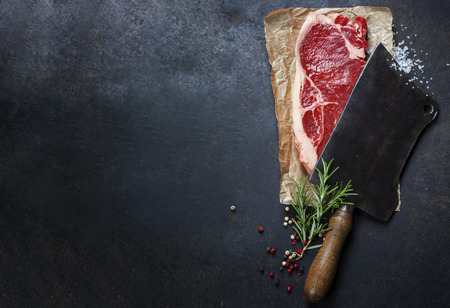 Foto de vintage cleaver and raw beef steak on dark background - Imagen libre de derechos