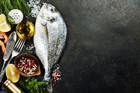 Foto de Delicious fresh fish on dark vintage background. Fish with aromatic herbs, spices and vegetables - healthy food, diet or cooking concept - Imagen libre de derechos