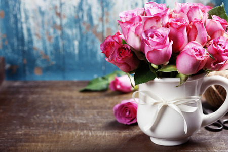Photo pour Pink roses in a pot on blue background - image libre de droit