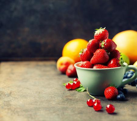 Foto de Strawberries in a cup and fresh fruits on rustic background - Imagen libre de derechos