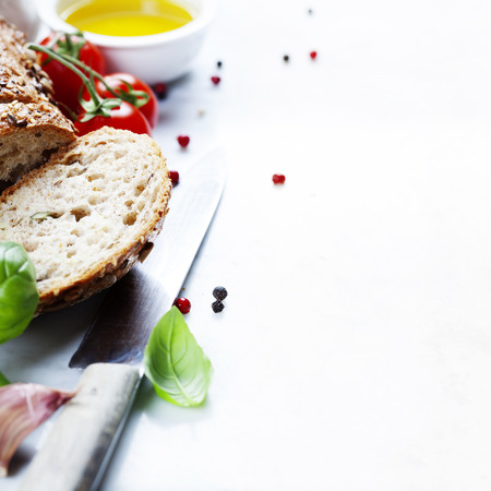 Foto de Tomato, bread, basil and olive oil on white marble background. Italian cooking, healthy food or vegetarian concept - Imagen libre de derechos