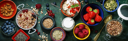 Foto de Healthy breakfast of muesli, berries with yogurt and seeds on dark background -  Healthy food, Diet, Detox, Clean Eating or Vegetarian concept. - Imagen libre de derechos
