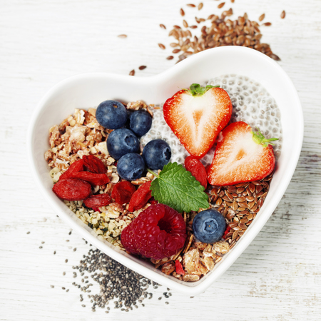 Photo pour Healthy breakfast of muesli, berries with yogurt and seeds on white background -  Healthy food, Diet, Detox, Clean Eating or Vegetarian concept.Top view - image libre de droit