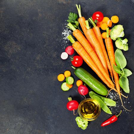 Foto de Fresh organic vegetables on dark rustic background. Healthy food. Vegetarian eating. Fresh harvest from the garden. Background layout with free text space. - Imagen libre de derechos