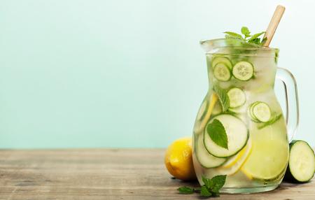 Foto de Infused water with cucumber, lemon, lime and mint on blue background - Imagen libre de derechos