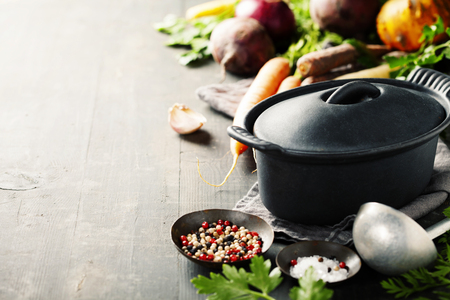 Photo pour Cast iron pot and vegetables on wooden rustic table. Homemade food, cooking, vegetarian concept - image libre de droit